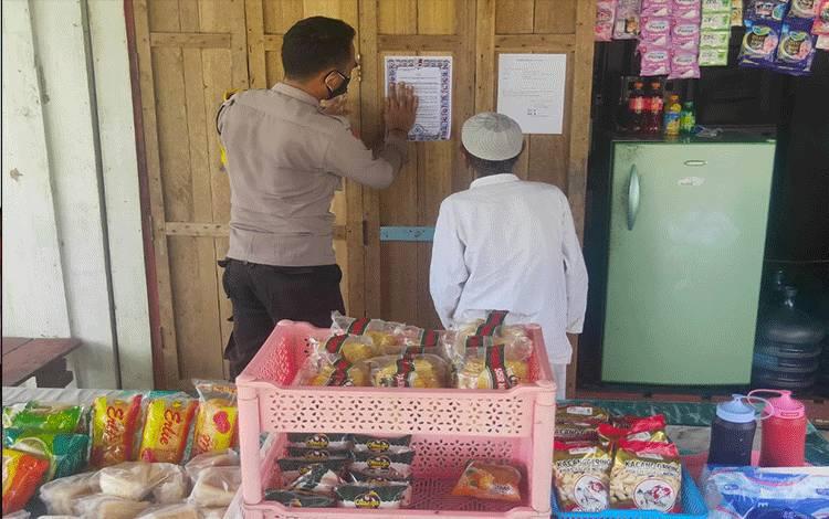 Bhabinkamtibmas Polsek Seruyan Hilir saat menempelkan Maklumat Kapolri saat sosialisasi di Desa Halimaung Jaya, Sabtu 2 Januari 2021.