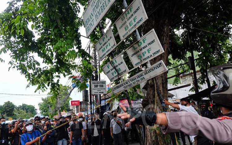 Polisi merobohkan plang Front Pembela Islam (FPI) di Petamburan, Jakarta, Rabu, 30 Desember 2020. Pasca pengumuman pemerintah membubarkan FPI, polisi menyisir area sekitar kantor DPP FPI dan di depan Rumah Rizieq Shihab di Jalan Paksi, Jakarta Pusat. TEMPO/Hilman Fathurrahman W