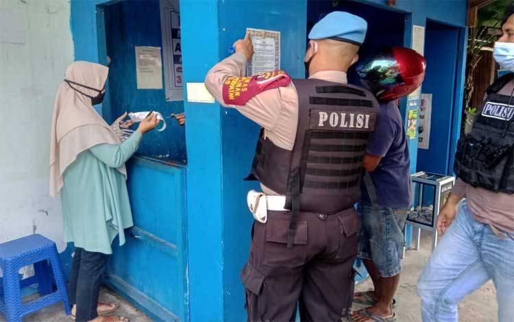 Personel Polsek Seruyan Hilir saat memasang Maklumat Kapolri di tempat umum