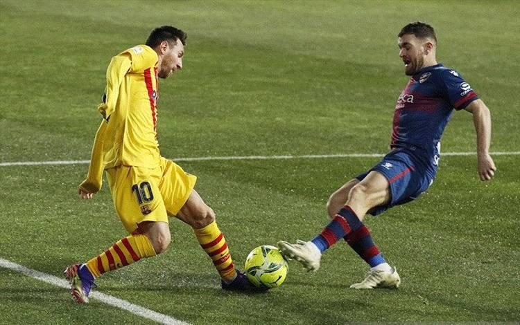 Megabintang Barcelona Lionel Messi (kiri) berusaha melewati hadangan bek Huesca Javi Galan dalam lanjutan Liga Spanyol di Stadion El Alcoraz, Huesca, Spanyol, Minggu (3/1/2021) waktu setempat. (ANTARA/REUTERS/Albert Gea)