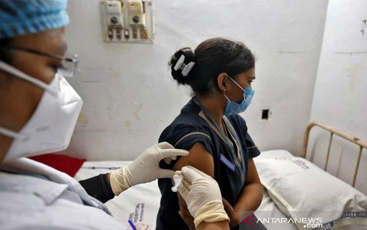 Seorang paramedis menyuntikkan vaksin anti penyakit virus corona (COVID-19) kepada seorang tenaga kesehatan dalam uji coba di Rumah Sakit Sipil di Ahmedabad, India, Selasa (5/1/2021). ANTARA FOTO/REUTERS/Amit Dave/hp/cfo