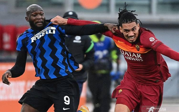 Bek AS Roma Chris Smalling (kanan) berduel dengan penyerang Inter Milan Romelu Lukaku pada pertandingan Liga Italia yang dimainkan di Stadion Olimpico, Roma, Minggu (10/1/2021). (ANTARA/AFP/VINCENZO PINTO)