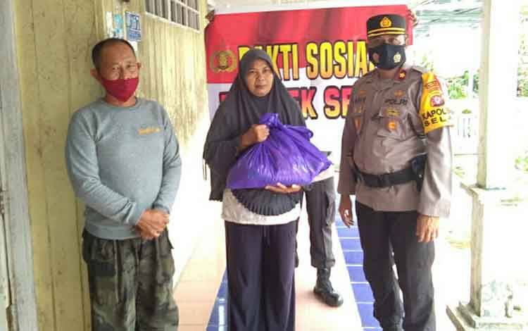 Kapolsek Selat Kompol Aris Setiyono saat menyalurkan bantuan sembako kepada warga di Kelurahan Selat Hulu.