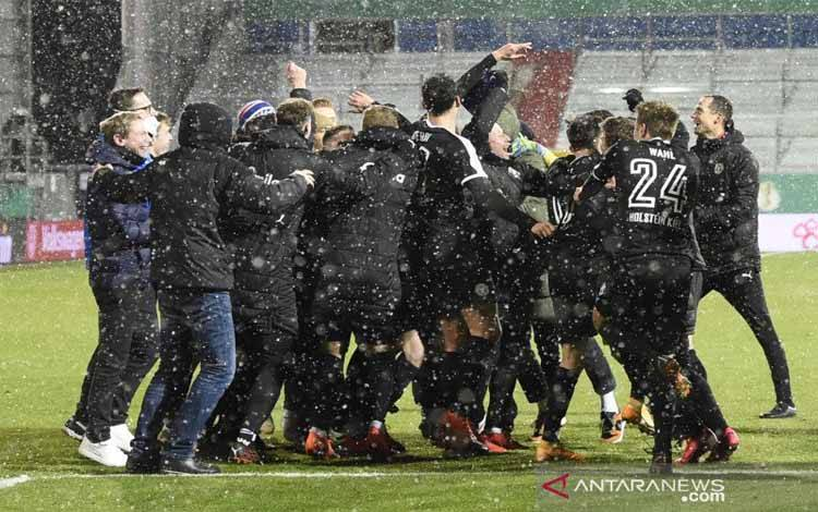 Para pemain Hosltein Kiel merayakan kemenangan mereka atas Bayern Munich pada pertandingan putaran kedua Piala Jerman yang dimainkan di Stadion Holstein Kiel, Hosltein, Rabu (13/1/2021)