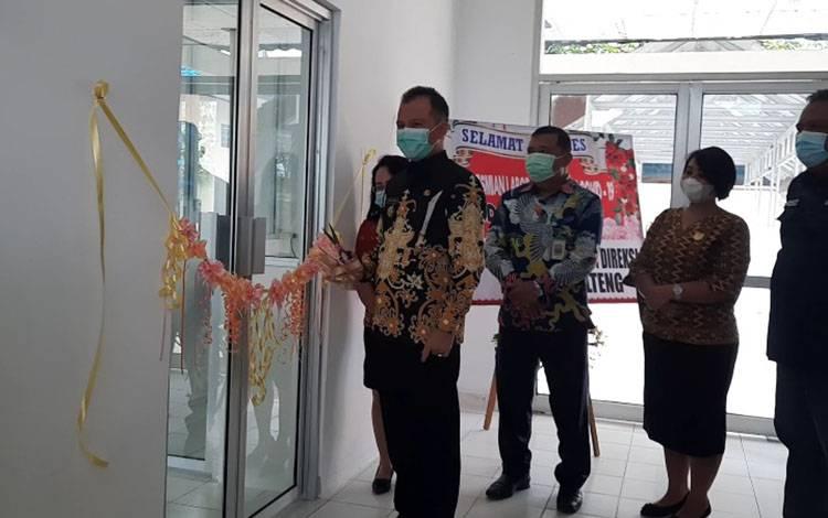 Bupati Gunung Mas Jaya S Monong menggunting pita peresmian laboratorium.