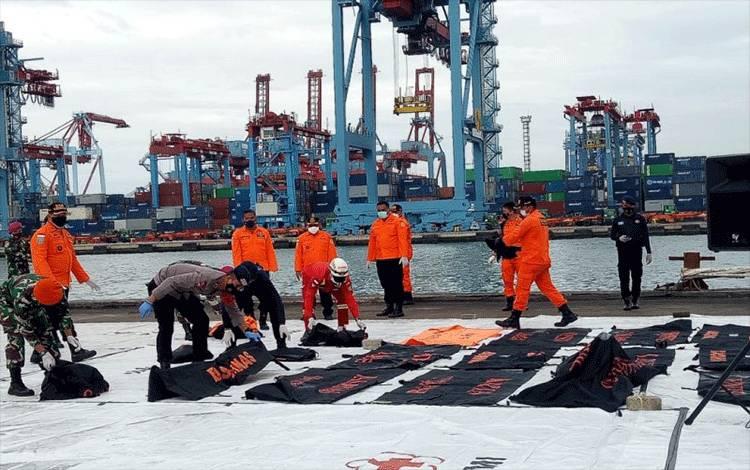 Tim SAR gabungan menyerahkan sejumlah kantong jenazah hasil operasi pencarian dan pertolongan kecelakaan pesawat Sriwijaya Air SJ182, pada hari keenam di JICT 2 Tanjung Priok, Jakarta, Kamis (14/1/2021) (ANTARA/Martha Herlinawati Simanjuntak)