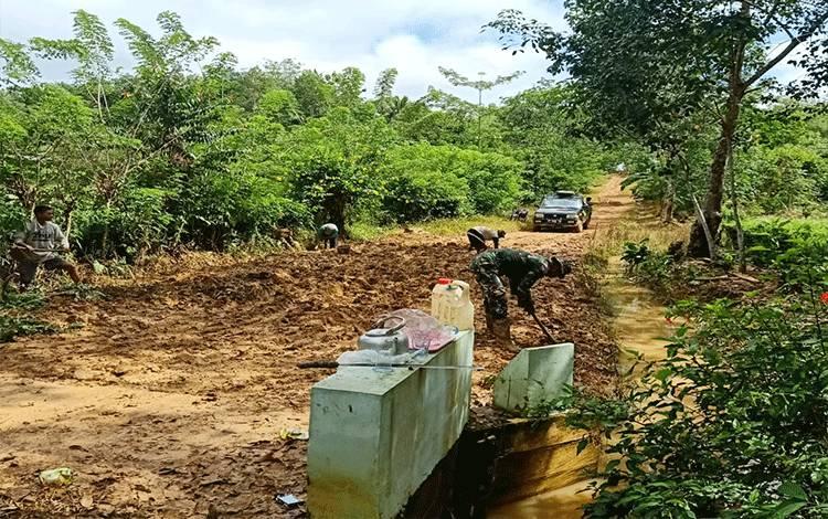 Anggota Koramil 1013-04/Benangin bersama warga saat gotong royong memperbaiki jalan penghubung dari pemukiman ke ladang masyarakat di Desa Mampuak II, Kecamatan Teweh Timur.