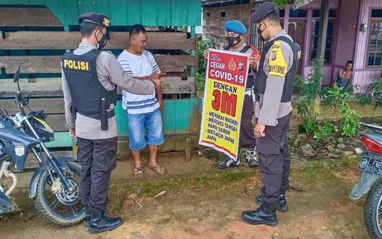 Personel Polsek Seruyan Hulu, saat memberikan sosialisasi protokol kesehatan kepada warga setempat.