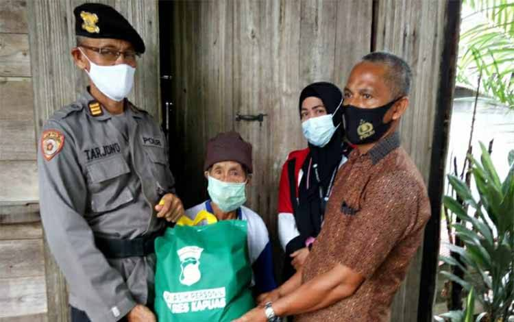 Personel Polres Kapuas menyalurkan bantuan paket sembako kepada warga Kecamatan Selat