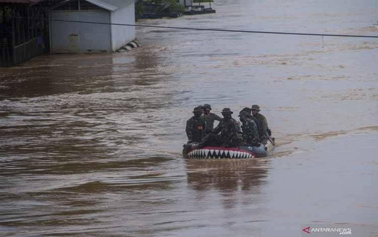 Sejumlah Prajurit Korps Marinir TNI AL Pasmar 1 Jakarta menggunakan perahu karet untuk mengevakuasi korban banjir di Desa Pekauman Ulu, Kabupaten Banjar, Kalimantan Selatan, Sabtu (16/1/2021)
