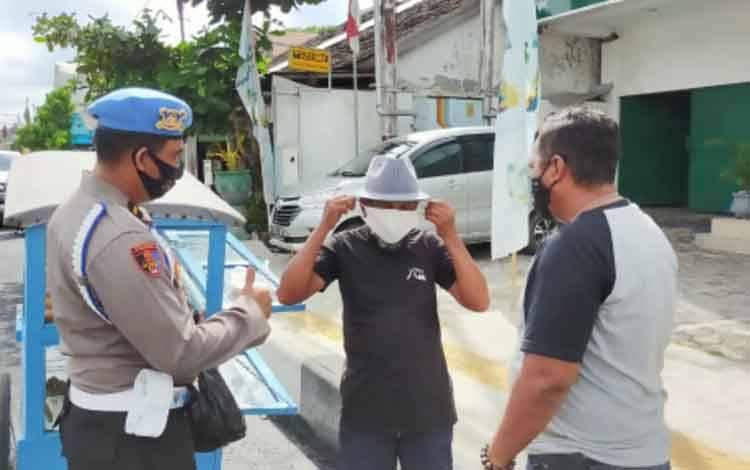 Sejumlah anggota kepolisian saat membagikan masker kepada warga