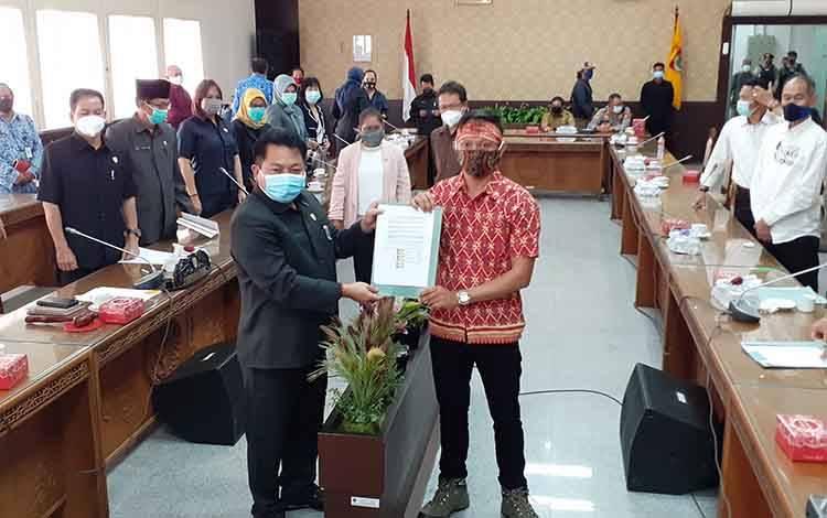 Ketua DPRD Kalteng, Wiyatno menerima salinan tuntutan yang diserahkan oleh koordinator lapangan aksi AMPKT, Rotama (kanan), Senin, 18 Januari 2021