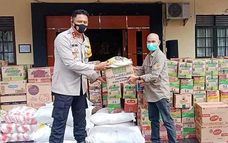 Hengky A Garu saat menyerahkan bantuan bagi korban bencana banjir melalui Kapolres AKBP Nur Khamid