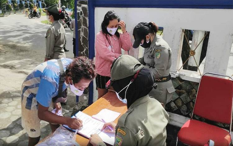 Tim pendisiplinan Covid-19 saat mendata warga yang kedapatan tidak menggunakan masker.