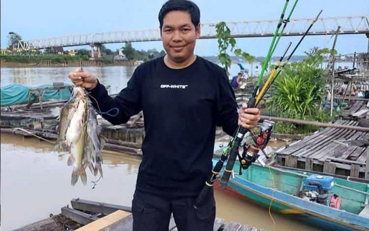 Seorang warga menunjukkan hasil tangkapan jenis ikan baung di Sungai Katingan sekitar Jembatan Sei Katingan.