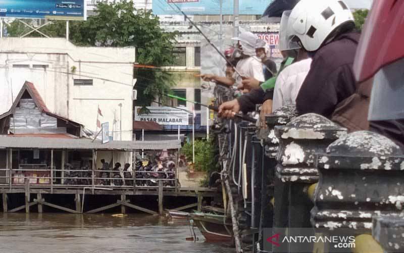 Warga memancing ikan yang akibat banjir lepas ke aliran Sungai Martapura dari Jembatan Pangeran Antasari di Kota Banjarmasin, Kalimantan Selatan. Jumat (22/1/2021).(foto : ANTARA/Sukarli)