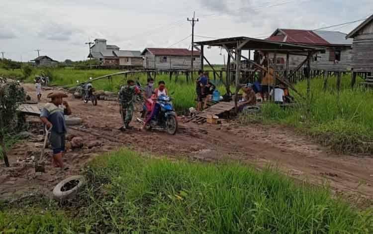 Babinsa Serma Agus Suseno bersama Lurah dan warga setempat saat gotong-royong memperbaiki jalan berlubang menuju Kampung Bereng Bengkel