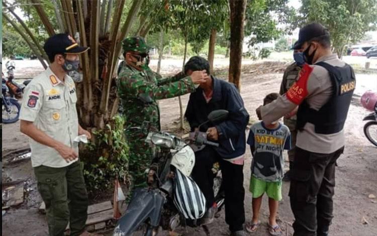 Tim gabungan memakaikan masker kepada pengendara roda dua saat patroli sinergitas hari ini.