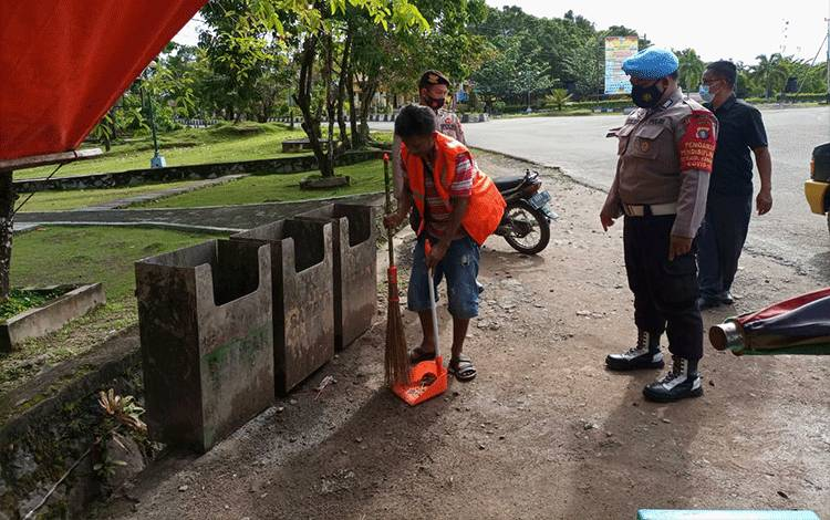 Aparat kepolisian memberikan teguran berikut sanksi sosial berupa menyapu kepada seorang warga dalam kegiatan Operasi Yustisi.