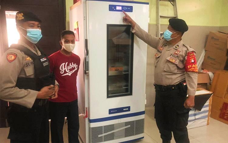 Personel Polresta Palangka Raya saat melakukan pengecekan suhu vaksin di lemari.