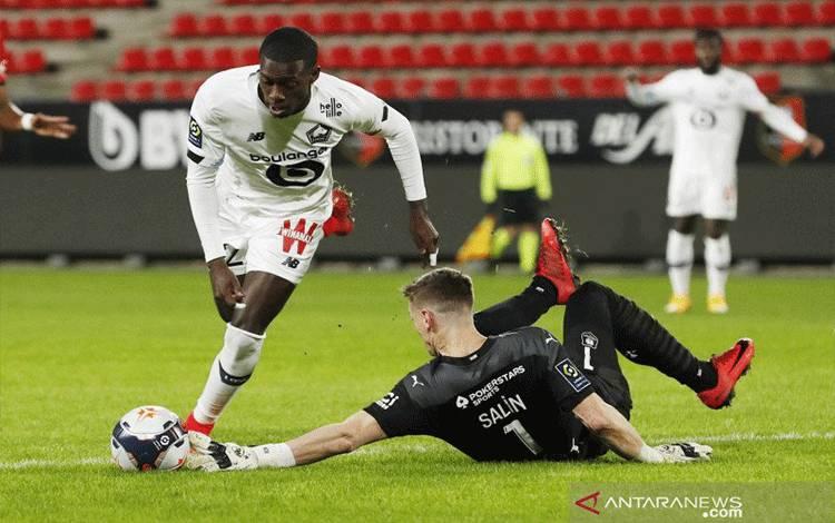 Aksi kiper Rennes Romain Salin saat menghadang laju bola yang dibawa pemain Lille Timothy Weah kala keduanya bertemu pada pekan ke-21 Liga Prancis di Stadion Roazhon Park, Minggu (24/1/2021). (ANTARA/REUTERS/STEPHANE MAHE)