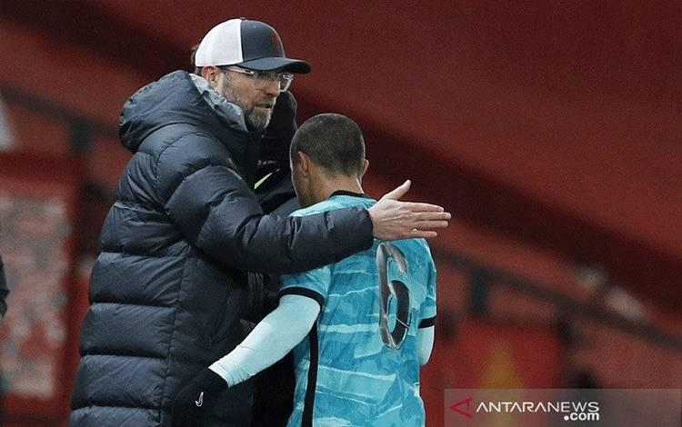 Manajer Liverpool Juergen Klopp (kiri) menyambut gelandang Thiago Alcantara yang ditarik keluar dalam laga putaran keempat Piala FA melawan Manchester United di Stadion Old Trafford, Manchester, Inggris, Minggu (24/1/2021) waktu setempat. (ANTARA/REUTERS/POOL/Phil Noble)