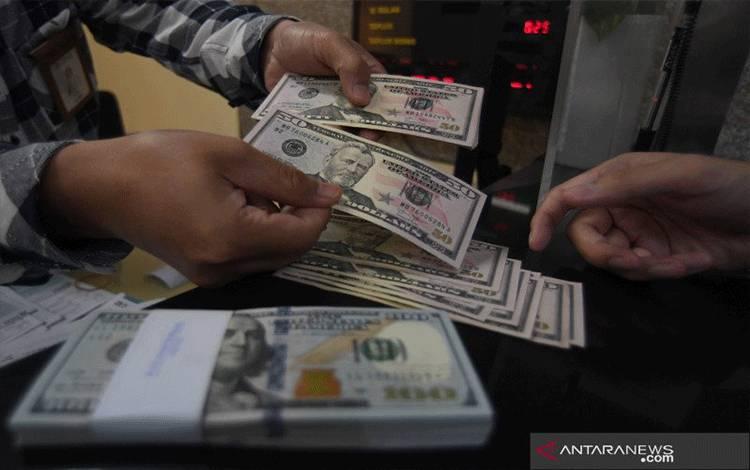Karyawan melayani pembelian uang dolar Amerika Serikat (AS) di sebuah tempat penukaran uang di Jakarta. ANTARA FOTO/Puspa Perwitasari/wsj.