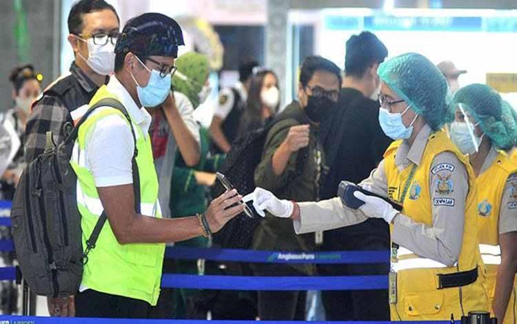 Menparekraf Sandiaga Uno menunjukkan dokumen persyaratan kesehatan kepada petugas KKP Kelas I Denpasar saat tiba di area Terminal Domestik Bandara Internasional I Gusti Ngurah Rai, Badung, Bali, Ahad, 27 Desember 2020. Dalam kunjungan tersebut, Menparekraf meninjau dan memastikan penerapan protokol kesehatan pencegahan COVID-19 bagi para wisatawan yang tiba di Pulau Dewata. ANTARA/Fikri Yusuf