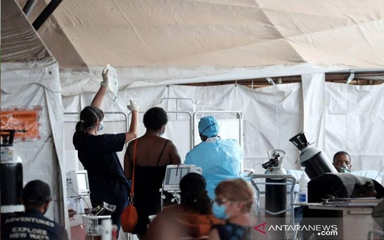 Petugas kesehatan mendampingi pasien di dalam tenda yang dipasang di lapangan parkir Rumah Sakit Akademi Steve Biko, ditengah penguncian nasional akibat wabah penyakit virus corona (COVID-19), di Pretoria, Afrika Selatan, Senin (11/1/2021). ANTARA FOTO/REUTERS/Siphiwe Sibeko/HP/djo