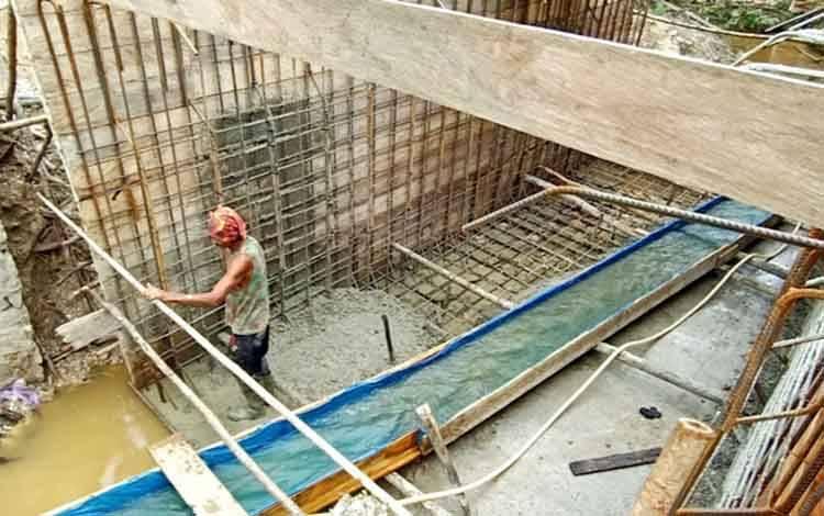 Salah seorang pekerja jembatan Desa Trinsing saat melakukan pengecoran plat lantai box culvert