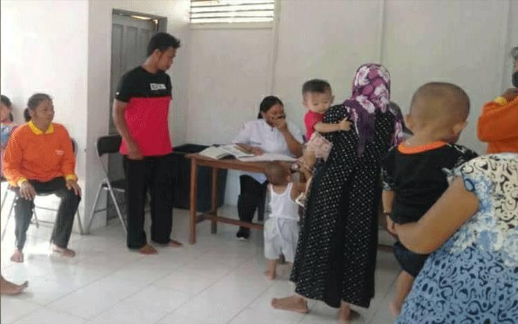 Pemberian susu untuk anak dan ibu hamil di kantor Pemerintah Desa Danau Rawah.