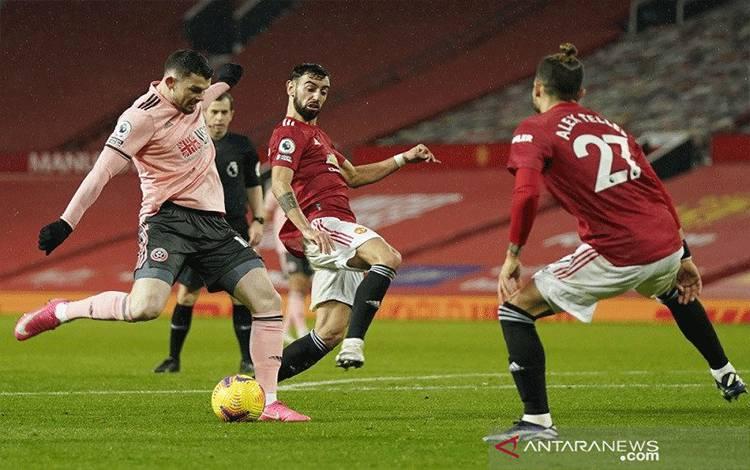 Penyerang Sheffield United Oliver Burke (kiri) melepaskan tembakan untuk mencetak gol kedua timnya ke gawang Manchester United dalam lanjutan Liga Inggris di Stadion Old Trafford, Manchester, Inggris, Rabu (27/1/2021) waktu setempat. (ANTARA/REUTERS/POOL/Tim Keeton)