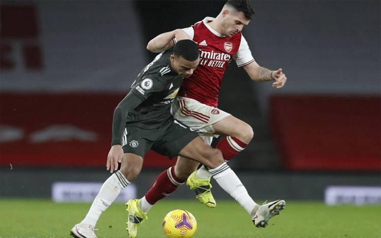Pemain Arsenal Granit Xhaka berduel dengan striker Manchester United Mason Greenwood dalam pertandingan Liga Inggris di Stadion Emirates, London, Inggris, 30 Januari 2021