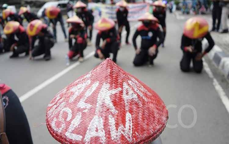 Massa dari Serikat Buruh menggelar aksi unjuk rasa di di kawasan Patung Kuda, Jakarta, Rabu, 16 Desember 2020. Mereka tampak membawa caping sebagai atribut saat berdemo menolak UU Cipta Kerja. TEMPO/Muhammad Hidayat