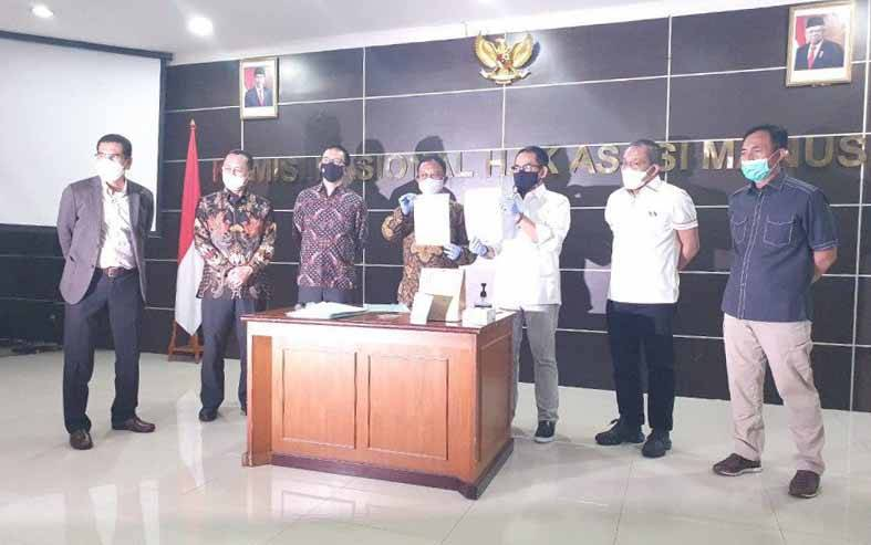 Ketua Tim Pemantauan dan Penyelidikan Komnas HAM Choirul Anam (tengah) secara simbolis menyerahkan barang bukti kasus tewasnya enam Laskar FPI kepada Direktur Tindak Pidana Umum Bareskrim Polri Brigjen Andi Rian Djajadi (ketiga kanan) di Kantor Komnas HAM, Jakarta, Selasa (16/2/2021). (foto : ANTARA/HO-Polri)