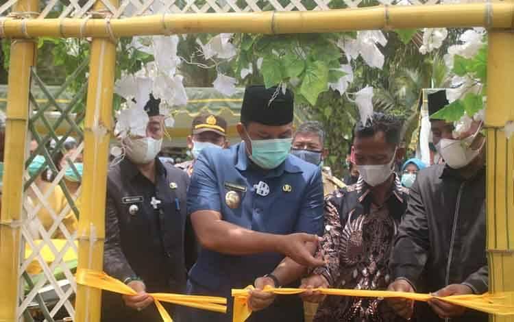 Bupati Hendra Lesmana didampingi Ketua DPRD dan Camat Bulik saat hadir dan menggunting pita pada acara syukuran dan tapungg tawar hasil pengelolaan kebun Desa Tamiang, Selasa 16 Februari 2021