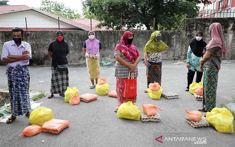 Para pengungsi Rohingya, dengan mengenakan masker dan menjaga jarak fisik, menunggu barang bantuan dari para relawan di Kuala Lumpur, Malaysia (7/4/2020), di tengah wabah virus corona (COVID-19). (foto : ANTARA/REUTERS/Lim Huey Teng/aa)