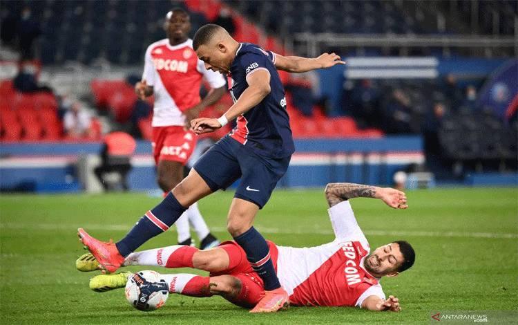 Pemain Paris Saint-Germain Kylian Mbappe saat dijegal bek Monaco Guillermo Maripan saat keduanya bertemu di pekan ke-26 Liga Pracis di Stadion Parc des Princes, Minggu (21/2/2021). (ANTARA/AFP/FRANCK FIFE)