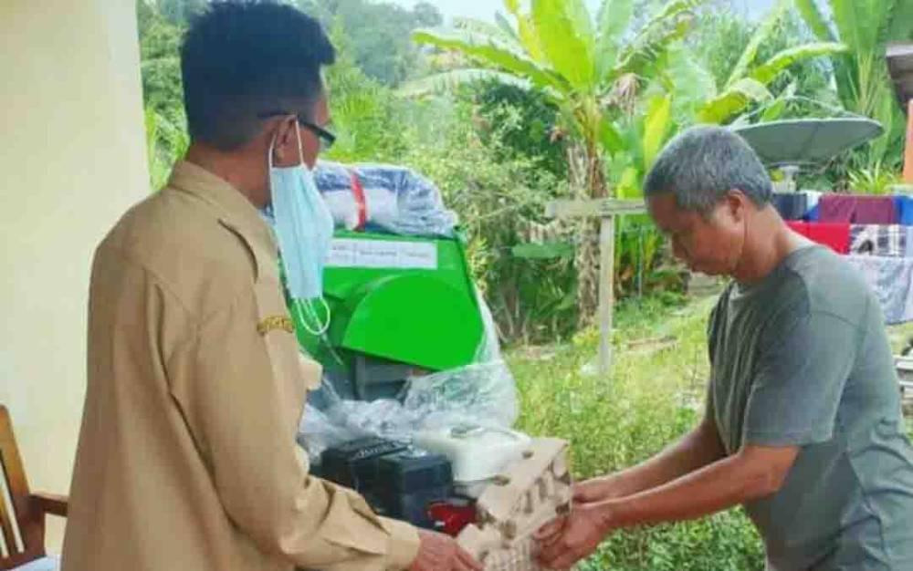 ket foto : pegawai Dinas Pertanian Barito Utara saat menyerahkan alsintan perontok padi kepada ketua kelompok tani.