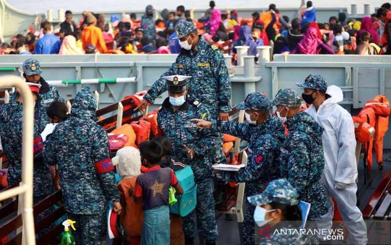 Petugas dari Angkatan Laut Bangladesh memeriksa para warga Rohingya sebelum mereka naik ke kapal untuk dipindahkan ke pulau Bhasan Char di Chattogram, Bangladesh, Selasa (29/12/2020). (foto : REUTERS/Mohammad Ponir Hossain/nz/cfo)