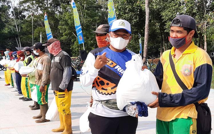 dr Fachruddin saat memberikan tali asih kepada petugas kebersihan, di sela - sela kegiatannya di area Jogging Track Lanud Iskandar Pangkalan Bun.