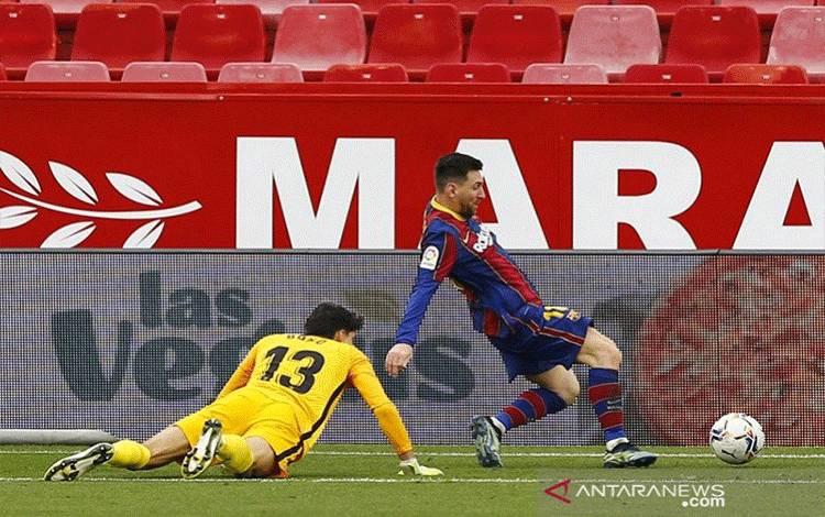 Megabintang Barcelona Lionel Messi (kanan) mengecoh kiper Sevilla Bono sebelum mencetak gol kedua timnya dalam laga lanjutan Liga Spanyol di Stadion Ramon Sanchez Pizjuan, Sevilla, Spanyol, Sabtu (27/2/2021). (ANTARA/REUTERS/Marcelo del Pozo)