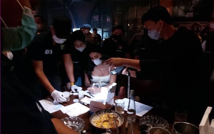 Selebgram Millen Cyrus (tengah) jalani tes urine saat terjaring razia protokol kesehatan yang dilaksanakan oleh Direktorat Reserse Narkoba Polda Metro Jaya di Bar Brotherhood Gunawarman, Kebayoran Baru, Jakarta Selatan, Minggu dini hari (28/2/2021). ANTARA/Fianda Rassat