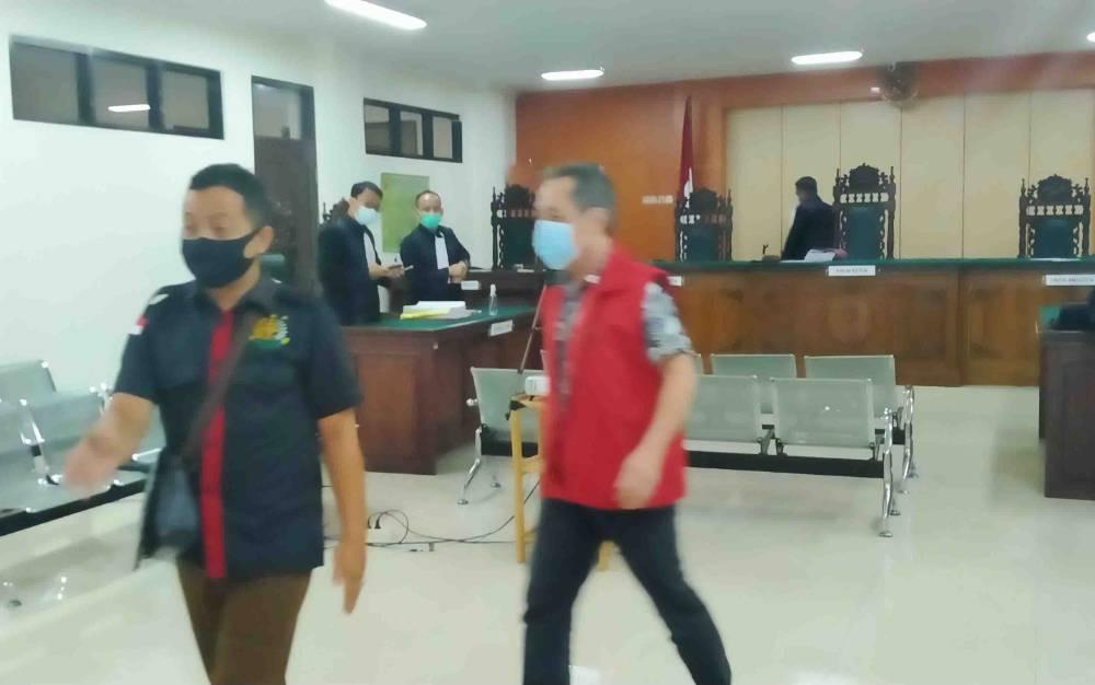 Bong Hiun Tjin alias Acin (rompi merah) saat meninggalkan ruang sidang.
