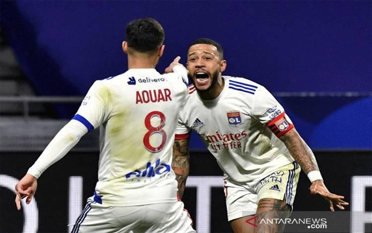 Gelandang serang Olympique Lyon Houssem Aouar (kiri) melakukan selebrasi bersama Memphis Depay seusai mencetak gol ke gawang Rennes dalam lanjutan Liga Prancis di Stadion Groupama, Lyon, Prancis, Rabu (3/3/2021) waktu setempat. (ANTARA/AFP/Philippe Desmazes)