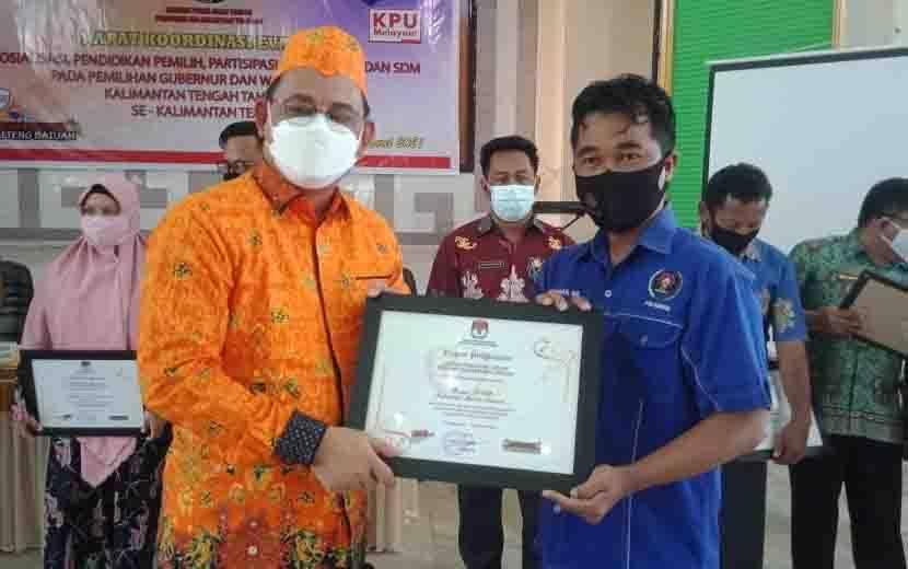 Ketua PWI Barsel, M. Hamdan (kanan) menerima piagam penghargaan dari Ketua KPU Kalteng, Harmain.