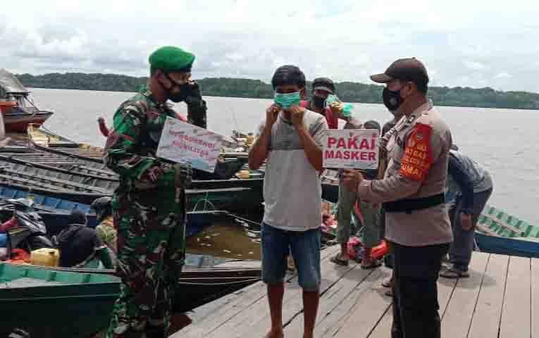Babinsa Koramil 1014-02 Kumai beserta personel Polsek Kumai, ingatkab prokes dan bagikan masker pada warga.