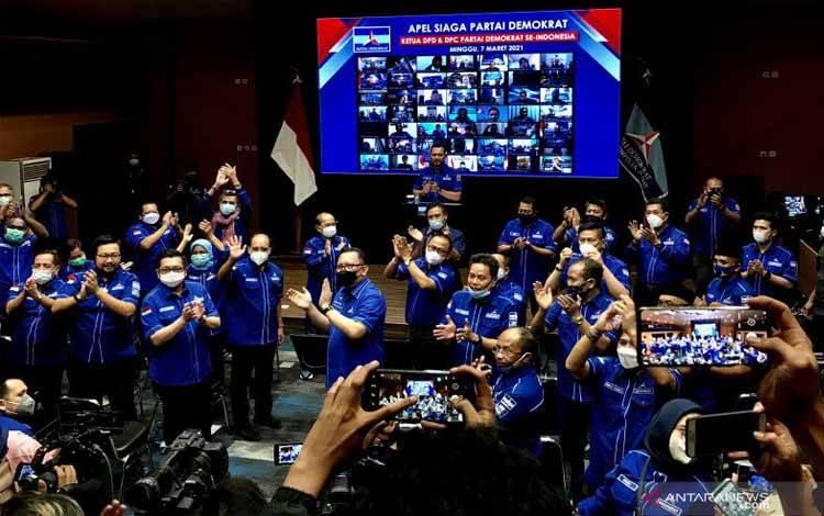 Ketua dan perwakilan dewan pimpinan daerah Partai Demokrat, Ketua Umum Partai Demokrat Agus Harimurti Yudhoyono-AHY (belakang tengah), dan ketua dewan pimpinan cabang (layar) bertepuk tangan saat bertemu dalam rapat konsolidasi partai, di kantor pusat Partai Demokrat, Jakarta, Minggu (7/3/2021)