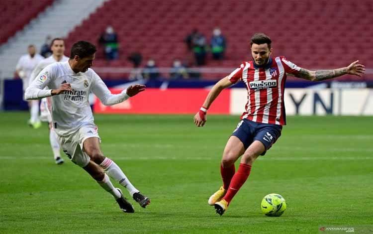 Bek Real Madrid Raphael Varane (kiri) berduel dengan gelandang Atletico Saul Niguez dalam pertandingan Liga Spanyol di Wanda Metropolitano, Madrid, Spanyol pada 7 Maret 2021