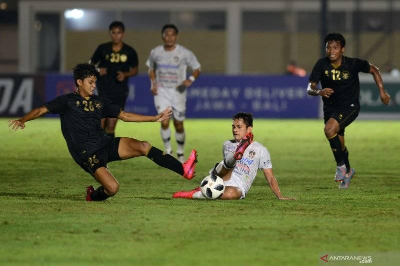 Pesepak bola Tim Nasional (Timnas) U-23 Hanif Syahbandi (kanan) berebut bola dengan pesepak bola klub Bali United Diego Assiss (tengah) dalam pertandingan uji coba di Stadion Madya, Gelora Bung Karno (GBK), Jakarta, Minggu (7/3/2021)